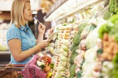 妇女读书购物单在超级市场 免版税图库摄影