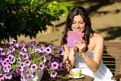 妇女读书ebook在庭院里 库存图片