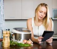 妇女读书ereader和烹调与crockpot 免版税库存图片