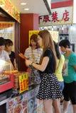 妇女购买在小吃店的香肠串在走的街道,广州市,瓷 图库摄影