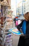 妇女购买查理Hebdo王牌从a的讽刺画报纸 免版税库存图片