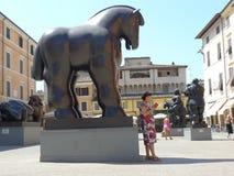 妇女读了一本书在Botero陈列下雕象在皮耶特拉桑塔意大利 免版税库存图片
