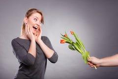 妇女从人得到郁金香花束  库存图片