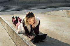 妇女年轻人的美好的关闭 白肤金发的女孩坐步在办公室外,拿着片剂 有笔记本的女性 库存图片