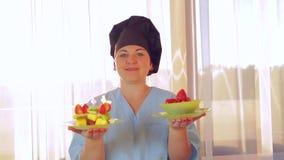妇女-厨师在她的手保留两块板材用果子点心 控制从窗口的阳光 照相机移动向dol 股票录像