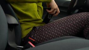 妇女紧固汽车安全安全带,当坐在车里面时在驾驶前 影视素材