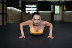 妇女从在健身房的地板推挤了 图库摄影