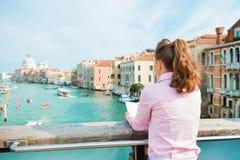 妇女从在大运河上的后面读书地图在威尼斯 免版税库存图片