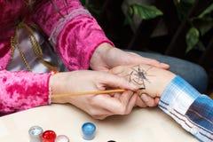 妇女画在女孩手上的蜘蛛 库存照片