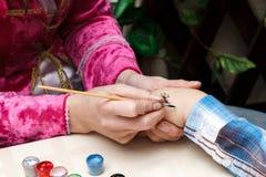妇女画在女孩手上的蜘蛛 库存图片