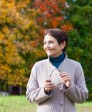 妇女50年在秋天公园 免版税库存照片