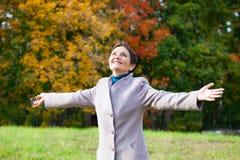妇女50年在秋天公园 免版税库存图片