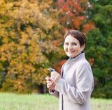 妇女50年在秋天公园 库存照片