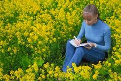 妇女画坐一棵草自白天 她绘坐油菜籽领域 库存照片
