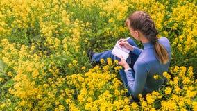 妇女画坐一棵草自白天 她绘坐油菜籽领域 免版税图库摄影