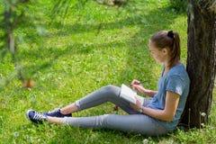 妇女画坐草 免版税库存照片