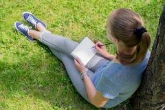 妇女画坐草 免版税图库摄影