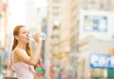 渴妇女 从塑料瓶的妇女饮用水在一个城市在夏日 库存照片
