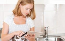 妇女主妇在有一台空白的片剂计算机的厨房里 免版税库存照片