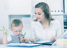 妇女22-27岁研究膝上型计算机,当儿童绘画时 免版税库存照片