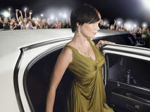 妇女离开在爱好者和无固定职业的摄影师前面的大型高级轿车 库存图片