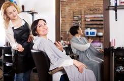 妇女满意对她的理发和年轻美发师 免版税库存照片