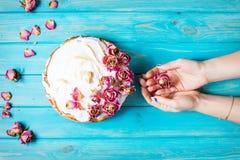 妇女`手举行干燥的s起来了 白色奶油色蛋糕在蓝色木背景装饰了干燥上升了 顶视图 免版税库存照片