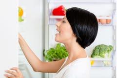 妇女寻找在被打开的冰箱的食物 免版税库存照片