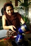 妇女从新近地被研的可可子手动地准备热的可可粉饮料 免版税图库摄影