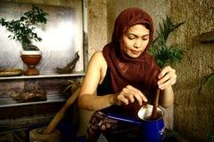 妇女从新近地被研的可可子手动地准备热的可可粉饮料 图库摄影