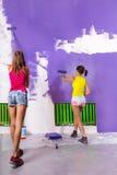 妇女绘有紫色漆滚筒的白色墙壁 库存照片