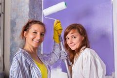 妇女绘有紫色漆滚筒的白色墙壁 免版税库存图片