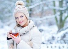 妇女水杯茶在冬天 免版税库存图片