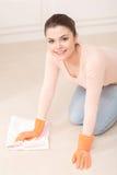 妇女洗涤在她的膝盖的地板 免版税库存图片