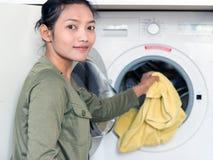 妇女洗涤在洗衣机的衣裳 免版税库存图片