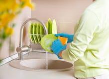 妇女洗涤的盘 库存照片