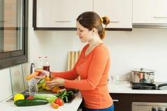 妇女洗涤的红萝卜 免版税库存图片