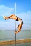 妇女锻炼反对海风景的杆舞蹈。 免版税库存照片