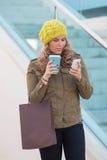 妇女购物用咖啡和电话 库存图片