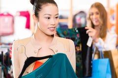 妇女购物衣裳在时尚商店 免版税库存图片