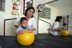 妇女医生在与有残障的男孩,巴西的工作 库存图片