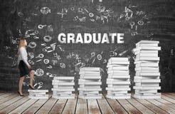 妇女去用完由白皮书制成的台阶 词毕业生是在黑黑板 库存照片