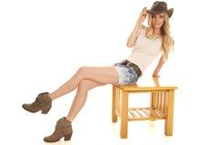 妇女轻的衬衣帽子短裤坐桌边 免版税库存照片
