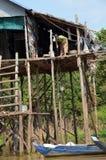 妇女从站立在他的高跷的房子里的河积水使用在一条长的绳索的桶 免版税库存图片