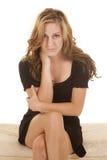 妇女黑色礼服坐面对严肃的发怒腿 图库摄影
