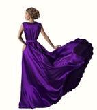 妇女紫色礼服,在丝绸褂子,挥动的织品,白色背景的时装模特儿 免版税库存图片
