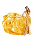 妇女黄色艺术丝绸礼服,看惊奇的女孩斜向一边 库存图片