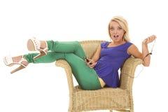 妇女绿色裤子耳机张嘴 免版税库存图片