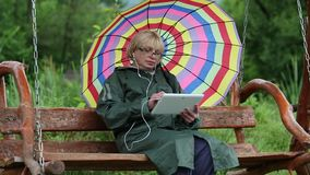 妇女绿色雨衣的和有伞的坐长凳并且使用片剂个人计算机 股票视频