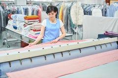 妇女洗衣店工作者轻拍在自动机器的亚麻布 免版税库存图片